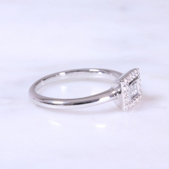 A contemporary horizontal baguette cut diamond set surround with round brilliant cuts in a halo ring